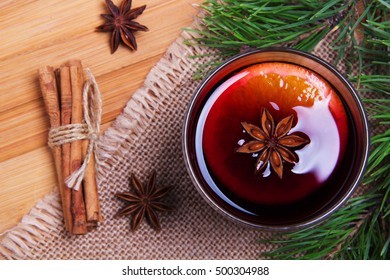 Glass of mulled wine with Anise star on wooden table top view
