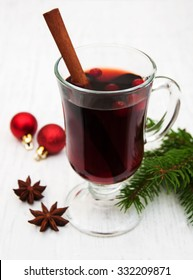 Glass of mulled wine and christmas decoration on a old wooden background