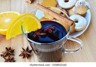 Glass of mulled wine with cinnamon sticks, star anise, cloves and Christmas cookies.