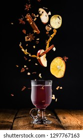 Glass of mulled wine with flying ingredients to prepare it on a black background