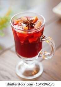 Glass of mulled wine with grapefruit, orange crusts and star anise or illicium seeds. Warming drink with or without alcohol.