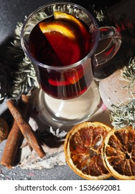 a glass of mulled wine on a dark background with cones, spices, the concept of the new year, powdered with snow.
