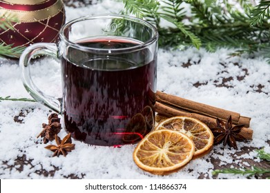 Glass with mulled wine on a snow covered background