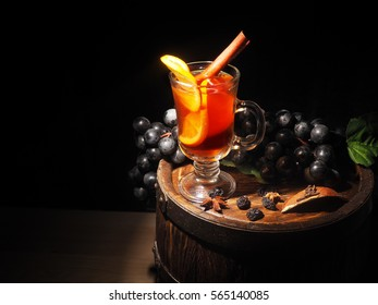 Glass of mulled wine on wooden barrel.