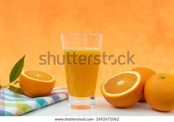 Glass of natural orange juice on orange background