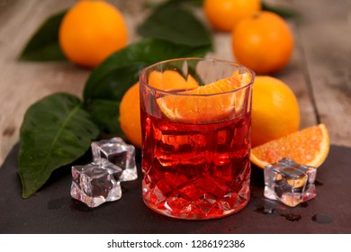 A glass of Negroni cocktail with Campari, Vermouth, Gin and Oranges. Alcoholic drink on dark stone table.