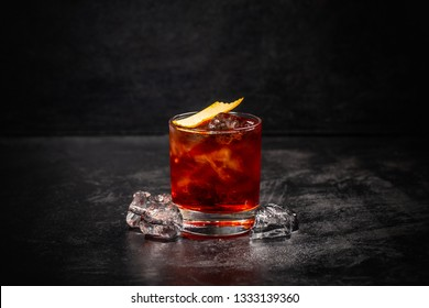 Glass of Negroni cocktail decorated with orange peel on dark background