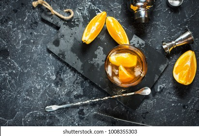 A glass of Negroni cocktail with orange and lemon. Alcoholic drink with rum and vermouth on dark stone table. With space for your text