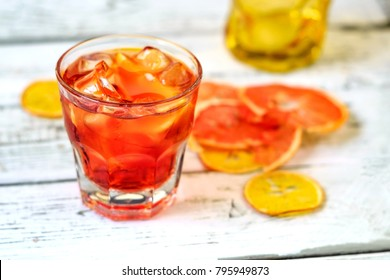 A glass of Negroni cocktail with orange and lemon. Alcoholic drink with rum and vermouth on white wooden background.