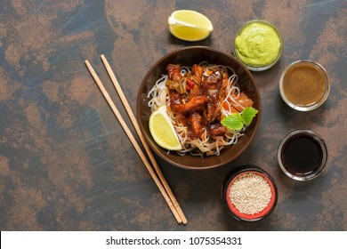 Glass noodles with vegetables and meat. Korean dish, top view. Stir-Fred Pork. Rustic rusty background, copy space