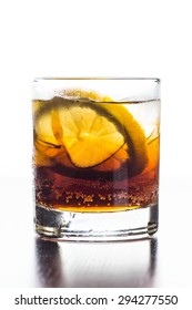 Glass of old fashioned cocktail with cola, ice and lemon slice
