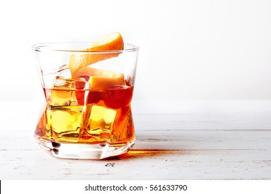 Glass of old fashioned whiskey over a white wooden table