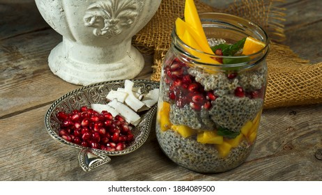 a glass on a wooden table with chiapudding, pomegranate and mango
