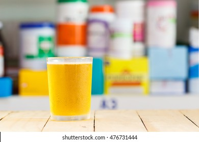 A glass of oral rehydration salts ( electrolyte drink ) on wooden with blurred medicine bottle background.health care concept