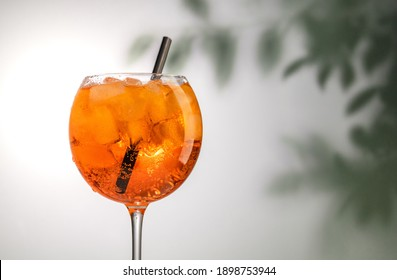glass of orange aperol spritz cocktail on defocused leaves background