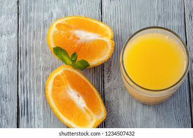 glass of orange freshness juice and orange slices on wooden background
