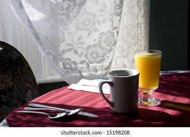 Glass of orange juice and cap of coffee on a table chair highlighted by the sunlight from  the window.