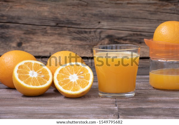 A glass of orange juice and the juicer