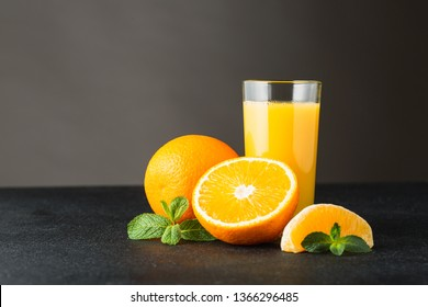 A glass of orange juice on a dark background.