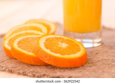 Glass of orange juice on wooden table and stylish cloth