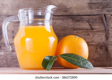 Glass of orange juice on wooden table, fresh drink