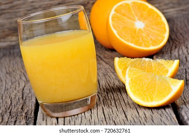 Glass with orange juice on wooden table close-up