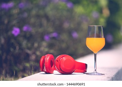 Glass of orange juice and red headphone on edge of swimming pool with blur flower and green tree in background. Copyspace on the left, process in vintage film style.