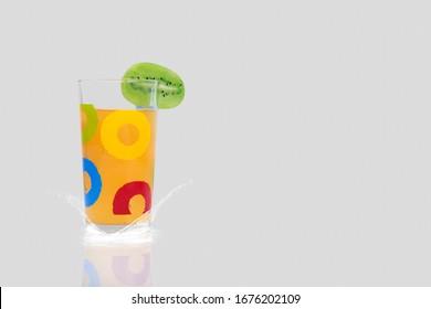 A glass of orange juice with a slice of kiwi