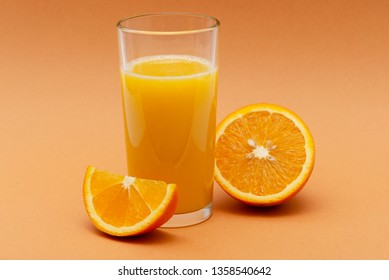 a glass of orange juice and a slice of orange on an orange background