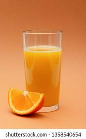 a glass of orange juice and a slice of orange on an orange background