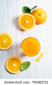 Glass of orange juice with sliced orange from above on white wooden background. fresh fruit product display.