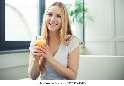 Glass of orange juice. Smiling beautiful young blond woman sitting at home on the couch with a glass of orange fresh.