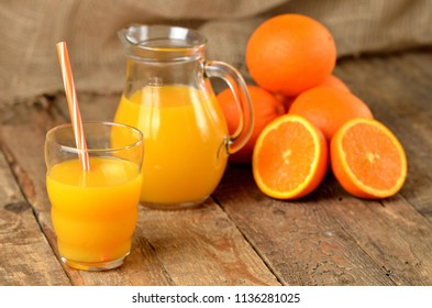 Glass with orange juice and straw, jug with fresh juice and pile of oranges in the background on wooden table