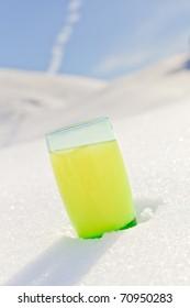 Glass of orange soda standing in snow mountain landscape with blue sky. Apres ski. Alps. France.