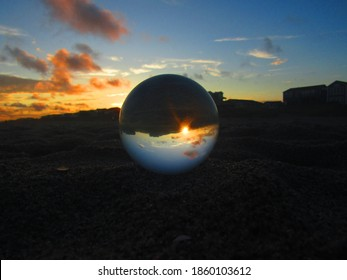 Glass orb on a beach at sunset