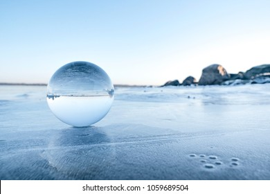 Glass orb on a frozen lake in the winter on a beautiful morning in the wintertime