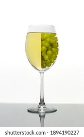 A glass ov white wine with grapes
