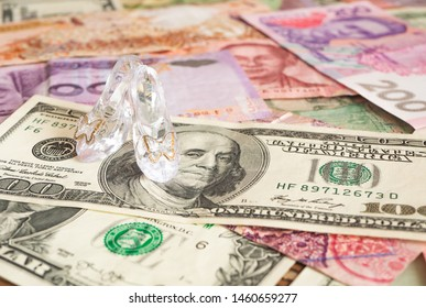 Glass pair of shoes on banknotes of different countries. Money for love. Prostitution
