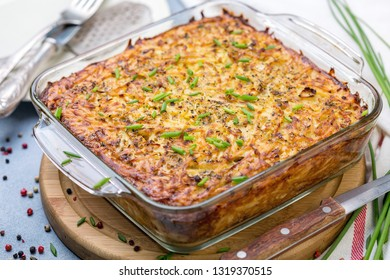 Glass pan with traditional potato kugel on wooden serving board, selective focus.