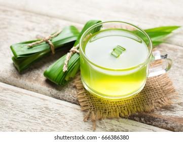 Glass of pandan juice and pandan leaves on wood background