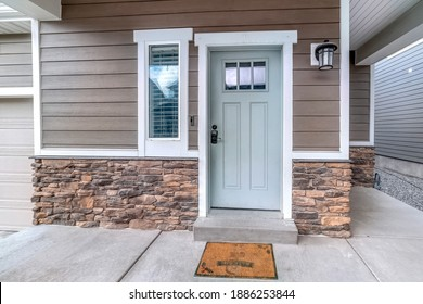 Glass paned front door and sidelight against brick wall and wood siding of home