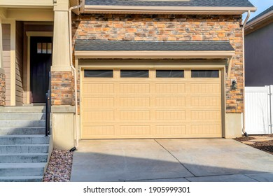 Glass paned front door and wide garage door of home with driveway and stairs