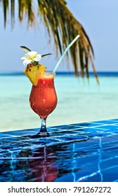 Glass of papaw juice is on edge of pool made from glazed tile  in tropical hotel, Maldives