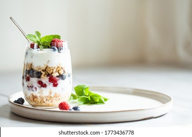 Glass of parfait made of granola, berries and yogurt on the table. Shot at angle with place for text, selective focus.