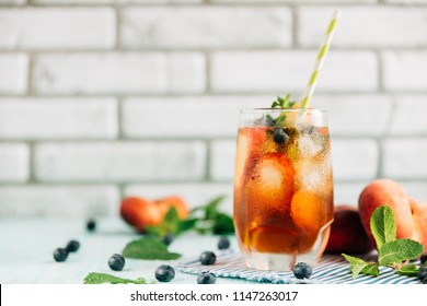 The glass of peach ice tea on wooden table. Cuba Libre or long island iced tea cocktail, cold drink or lemonade with fruits and mint, bilberry, blueberry