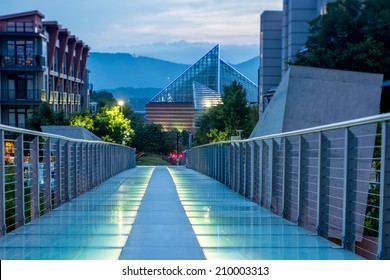 Glass pedestrian bridge between Walnut Street and High Street in Chattanooga Tennessee just after sunset. Ground in focus along the length of the bridge. Tennessee Aquarium in background.