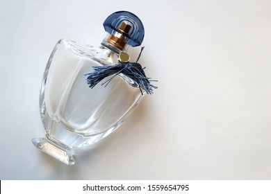 Glass perfume bottle with blue fringe isolated on white background with a copy space