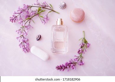 glass perfume bottle with delicate lilac flowers on a textured surface lit by the sun. Top  view