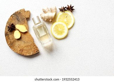 glass perfume bottle with lemon wedges, anise stars, wood bark and ginger fragments on beige background. fresh, woody, spicy unisex scent concept. Copy space