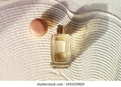 glass perfume bottle on a sandy textured background with long shadow. Summer vocation fragrance concept